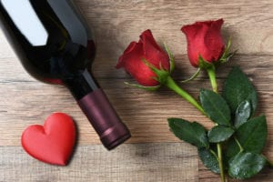 A wine bottle and two red roses and heart on a rustic wood table. Overhead view in horizontal format. Valentines Day Concept.